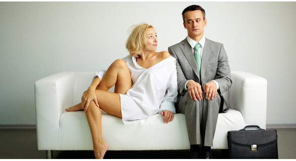 Photo of serious man sitting on sofa with seductive woman looking at him