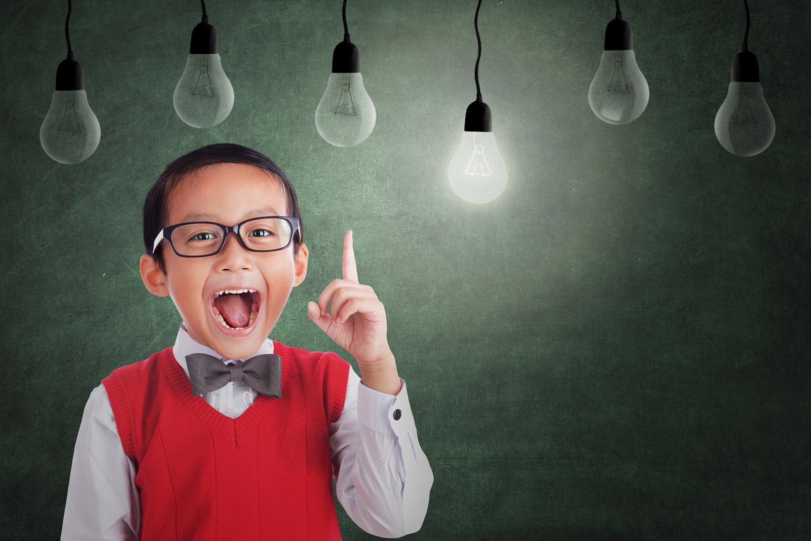 Asian student boy has an idea under light bulbs in class